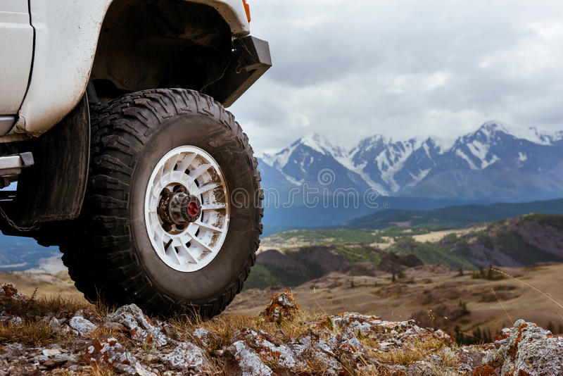 Big car wheel on background of mountains stock images