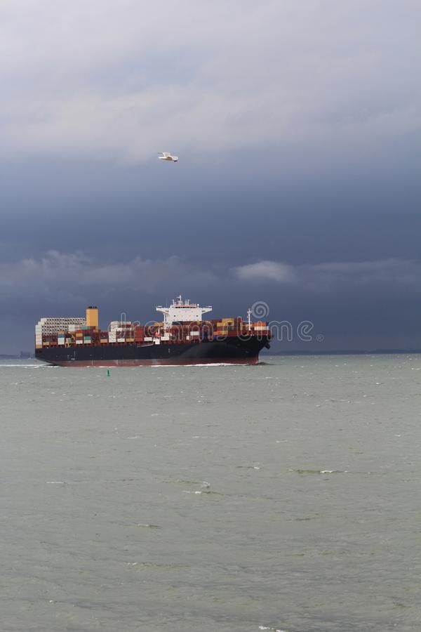 A big cargo ship navigates through the sea at a stormy day. A big dark blue container ship is navigating through the westerschelde towards antwerp at a stormy stock image