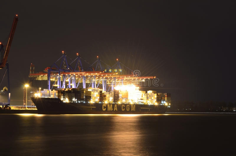 Forwarding port activity by night in Germany. Cranes unload a big container ship in Hamburg port terminal in Germany royalty free stock image