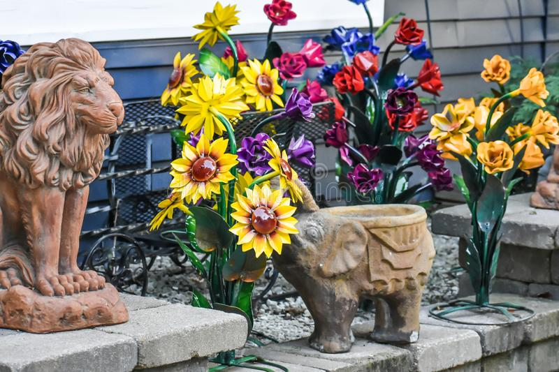 Big Cat Lion and Elephant Sculptures in Garden with Sunflowers. Cement, big cat, lion and elephant sculptures in a garden with a stone staircase and sunflowers royalty free stock photography
