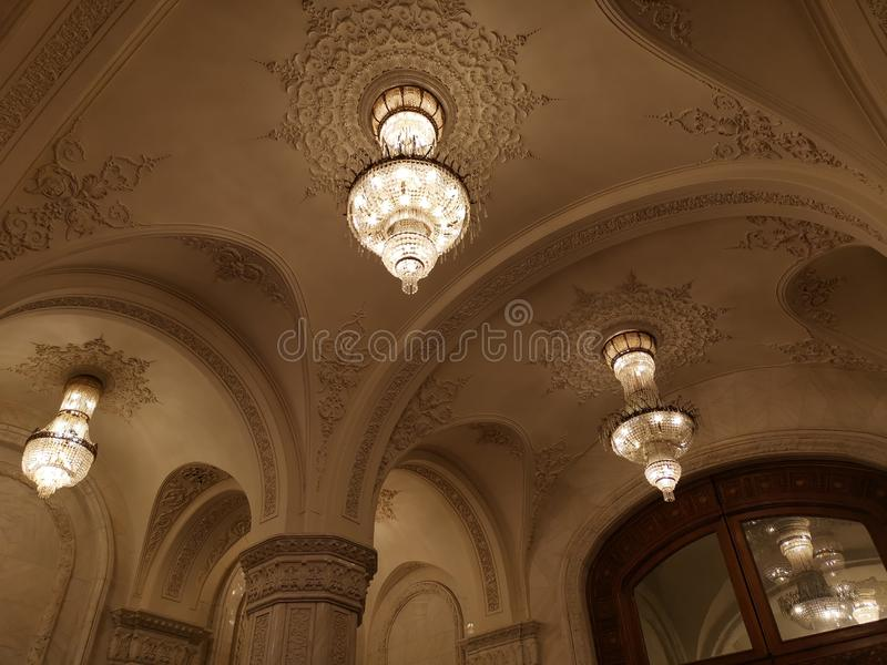 Big chandeliers and door with glass on the top. The reflection of the chandeliers in the door glass royalty free stock photo