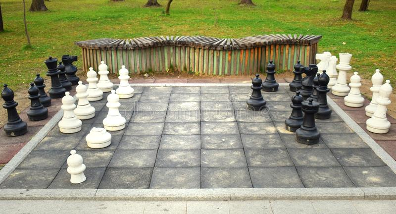 Big chess board with huge pieces in the park stock image