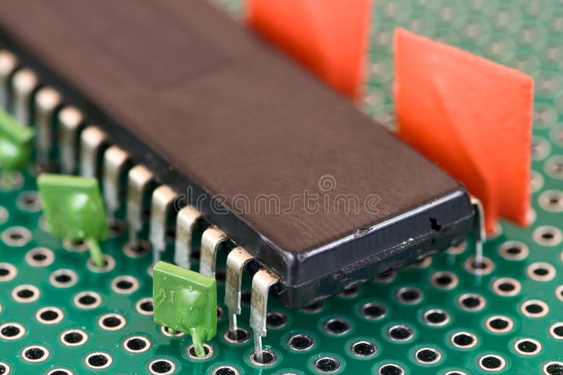 Big chip and capacitors on Printed Circuit Board. Big vintage chip and capacitors on Printed Circuit Board royalty free stock photo