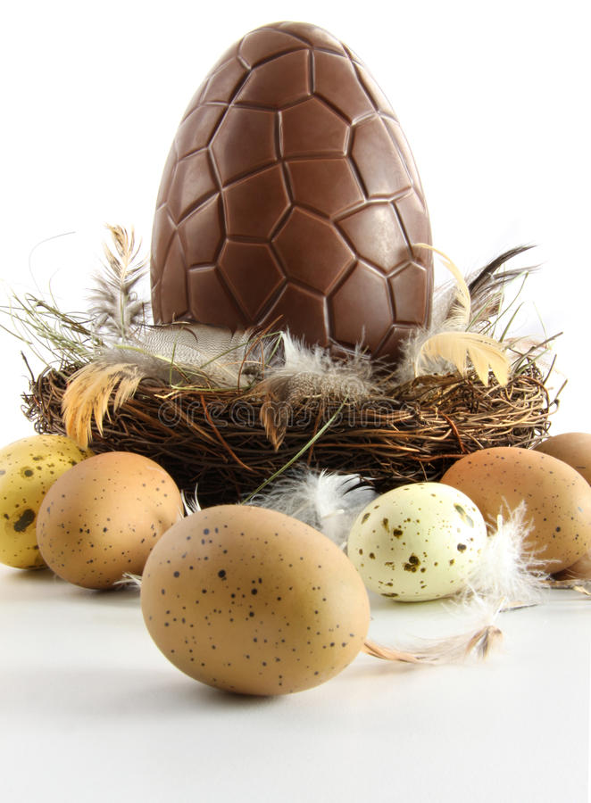 Big chocolate easter egg in nest with feathers royalty free stock images