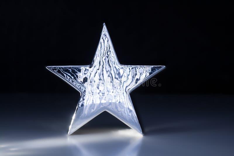 Big christmas silver metallic star dark black background light effects royalty free stock image