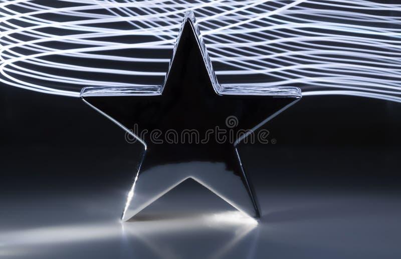 Big christmas silver metallic star dark grey background light effects stock images