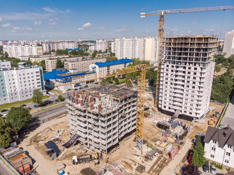 Big city construction site with cranes, machinery and workers stock image