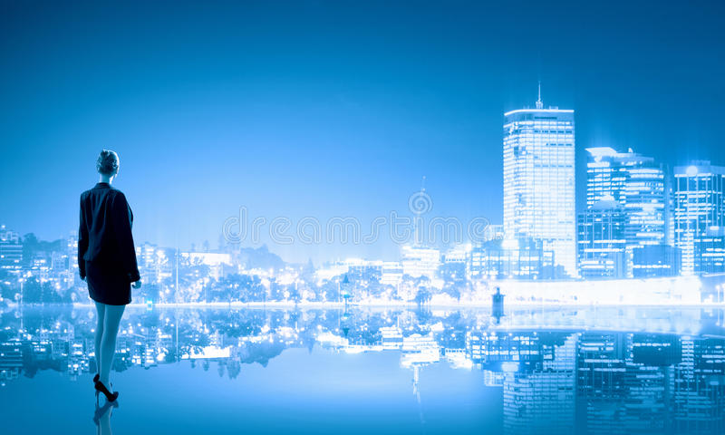Big city never sleeps. Businesswoman standing with back against night city panoramic view royalty free stock images