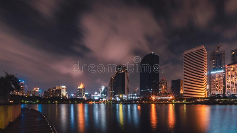 Big city in the night life with reflection of water wave. Long e royalty free stock image
