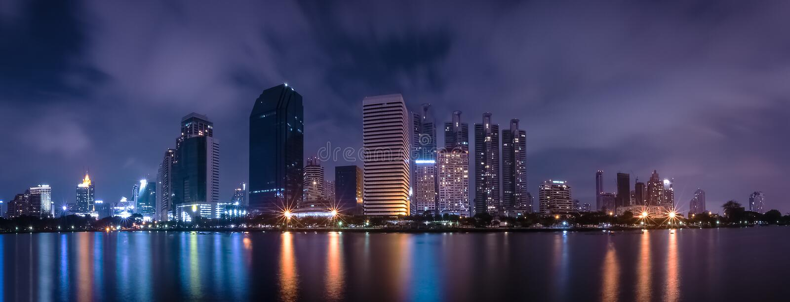 Big city in the night life with reflection of water wave. Long exposure Technics. Panorama of landscape.Town and urban concept. stock image