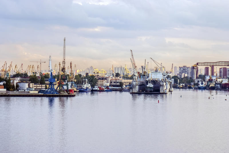 Big city sea port!. Photo of a big city industry sea port. Many huge yellow and red construction cranes, different machinery and cargo equipment, metal royalty free stock photography