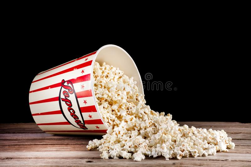 Spilled box with popcorn on retro wooden desk and black. Big classic spilled box with popcorn on retro wooden desk and black background. Space for text and royalty free stock images