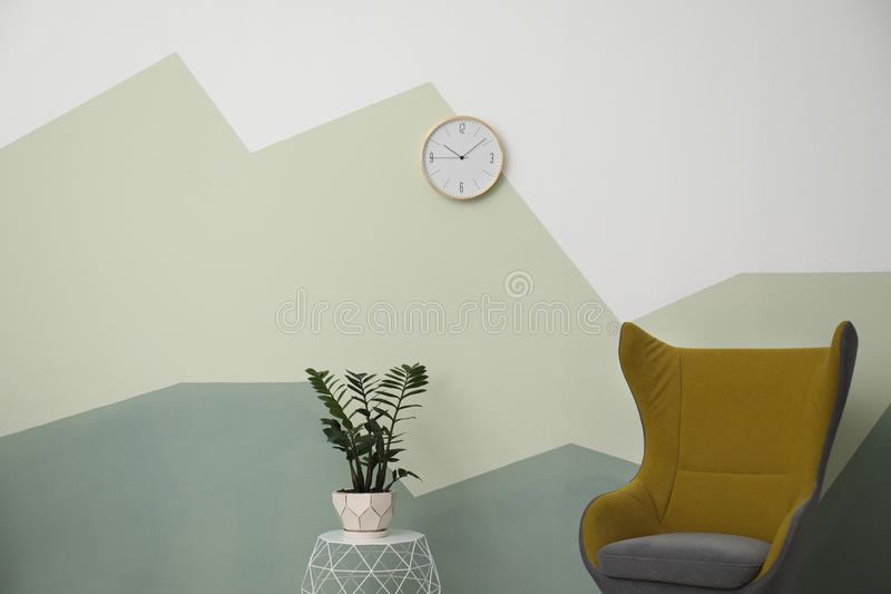 Big clock hanging on color wall stock photography