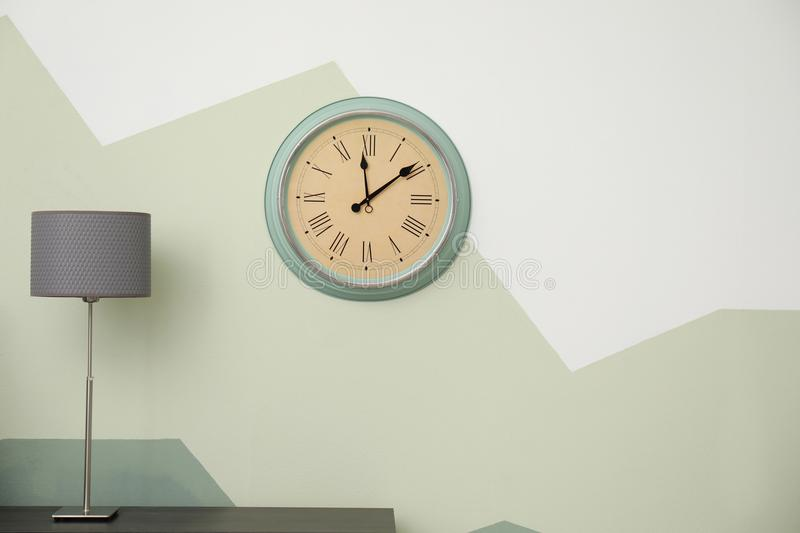 Big clock hanging on color wall stock image