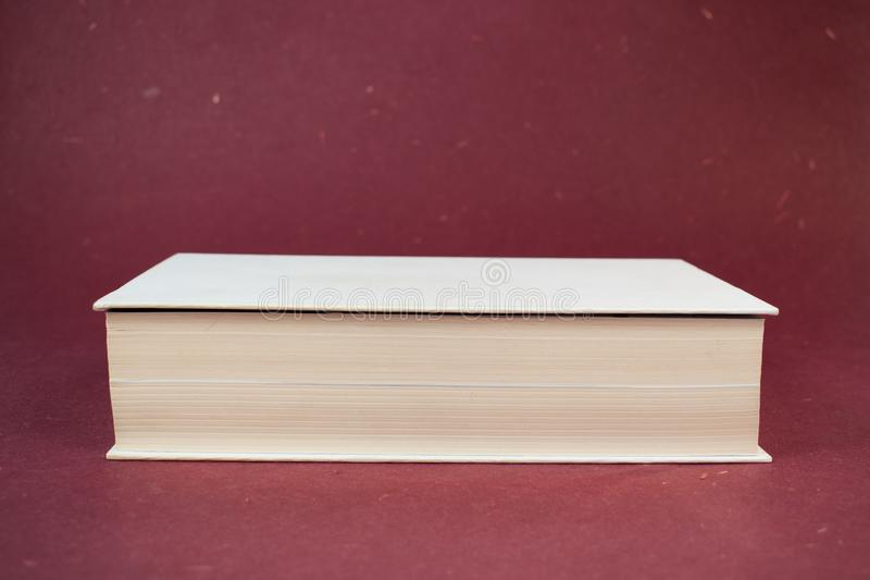 Big closed white hardcover book on red background stock image