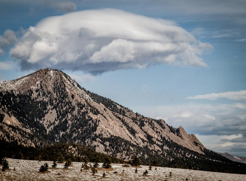 Mountain cloud. Big cloud hovering over mountain peak stock photography