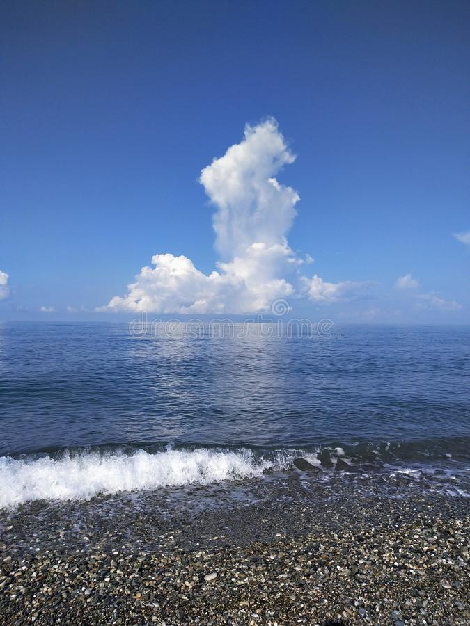 Big cloud over the horizon on the Black Sea. Big cloud  the horizon on the black sea, water, blue, transparent, sky, skyline, white, pebble, wave royalty free stock images