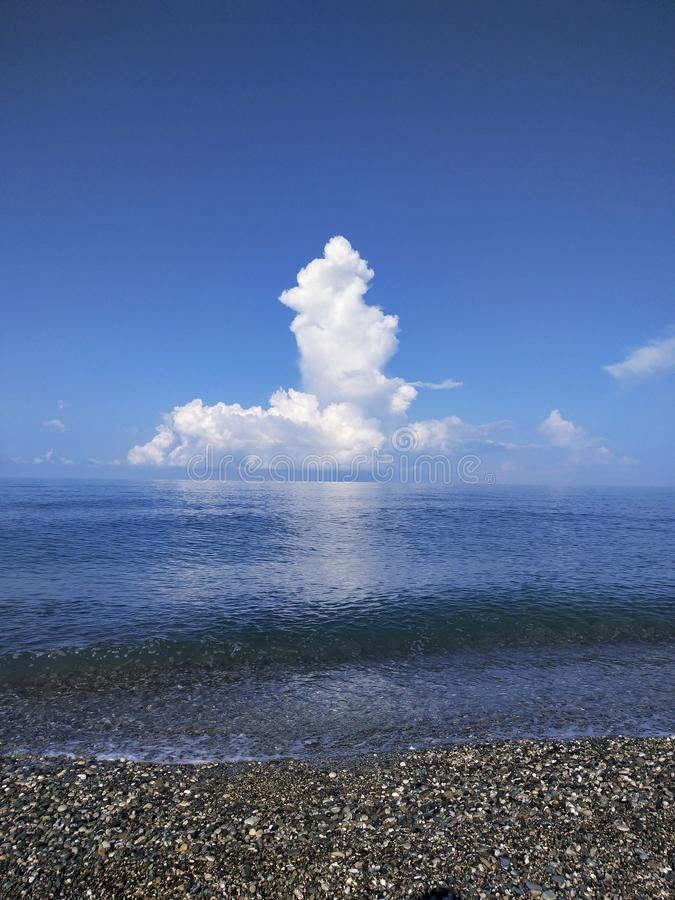 Big cloud over the horizon on the Black Sea. Big cloud  the horizon on the black sea, water, blue, transparent, sky, skyline, white, pebble, wave stock photos