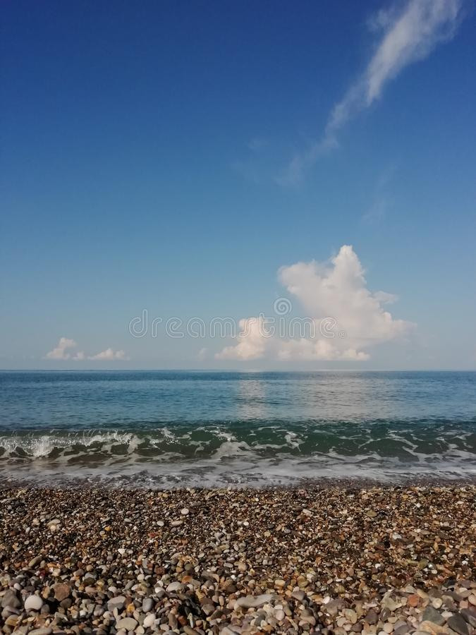 Big cloud over the horizon on the Black Sea. Big cloud  the horizon on the black sea, water, blue, transparent, sky, skyline, white, pebble, wave, reflection stock images