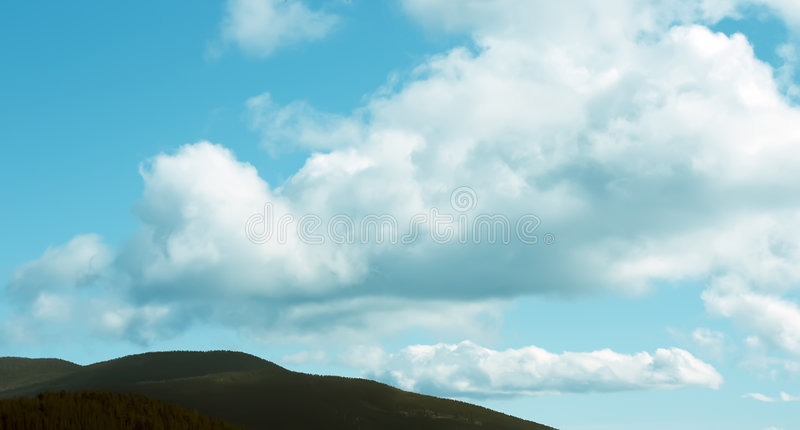 Big clouds. In green mountains in sunny day stock photo