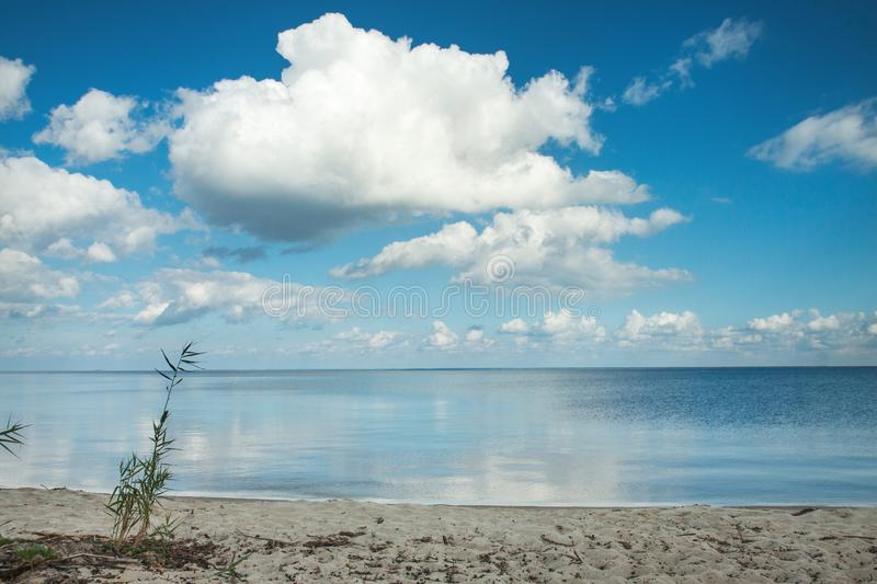Big clouds reflecting on the smooth water surface. Warm autumn day near the lake or a sea. Sandy shore near the water on a windless day stock photos