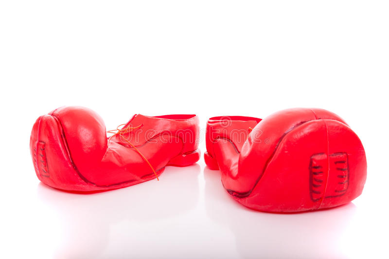 Big clown shoes. Small child legs inside a pair of big clown shoes (isolated on white royalty free stock photo