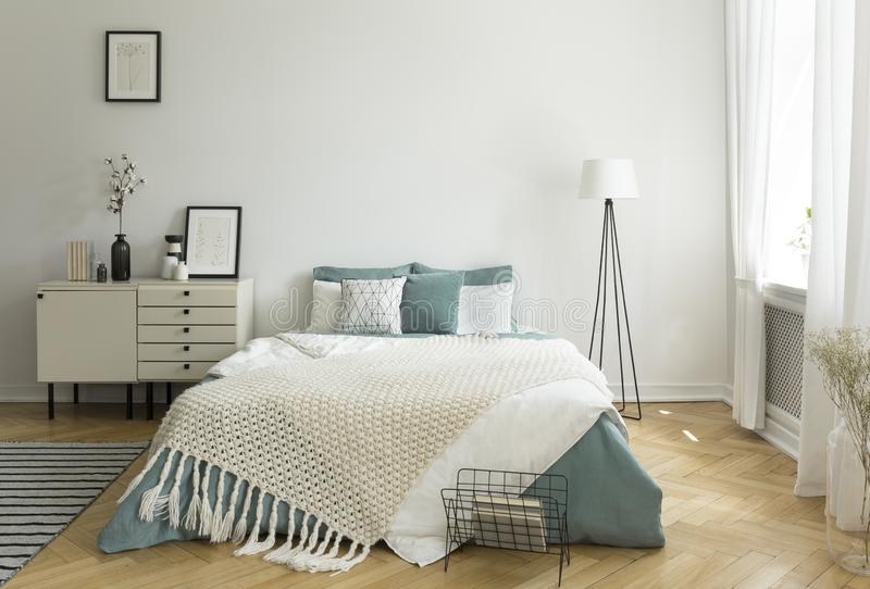 A big comfortable bed with pale sage green and white linen, pillows and blanket in a woman`s bright bedroom interior with windows royalty free stock photo