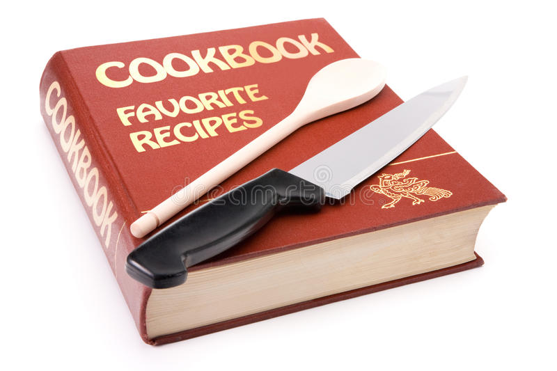 Big cookbook with wooden spoon and kitchen knife royalty free stock photography