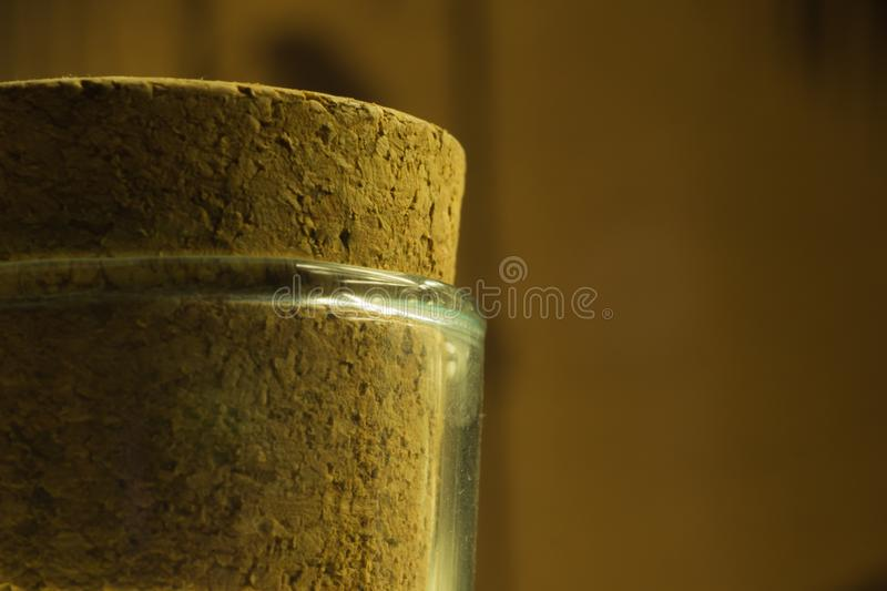 Big cork in the glass bottle close up. Background, jar, object, empty, stopper, container, transparent, canister, clear, plain, translucent, unlabeled, little royalty free stock images