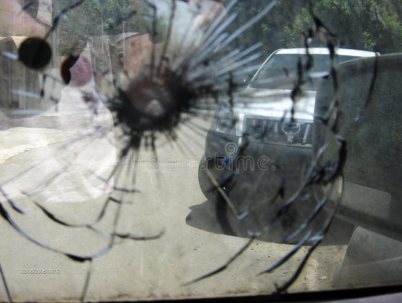 Big crack to windshield of car from fragment military sniper bullet stock photo