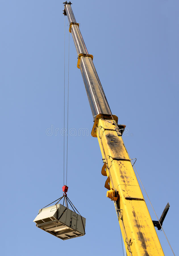 Big Crane. A large crane being used to remove a air conditioning unit from a commercial building stock images