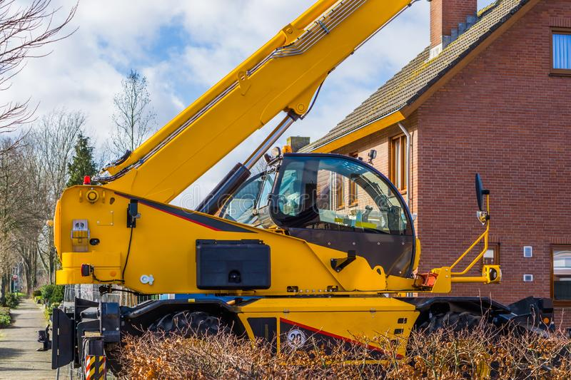 Big crane machine with view on the cabin parked in a neighborhood, heavy construction machinery royalty free stock photos