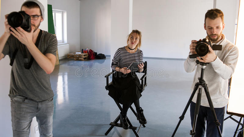 Big creative team working in studio. Photographer and videographer working while art director observing. Production of commercials backstage royalty free stock image