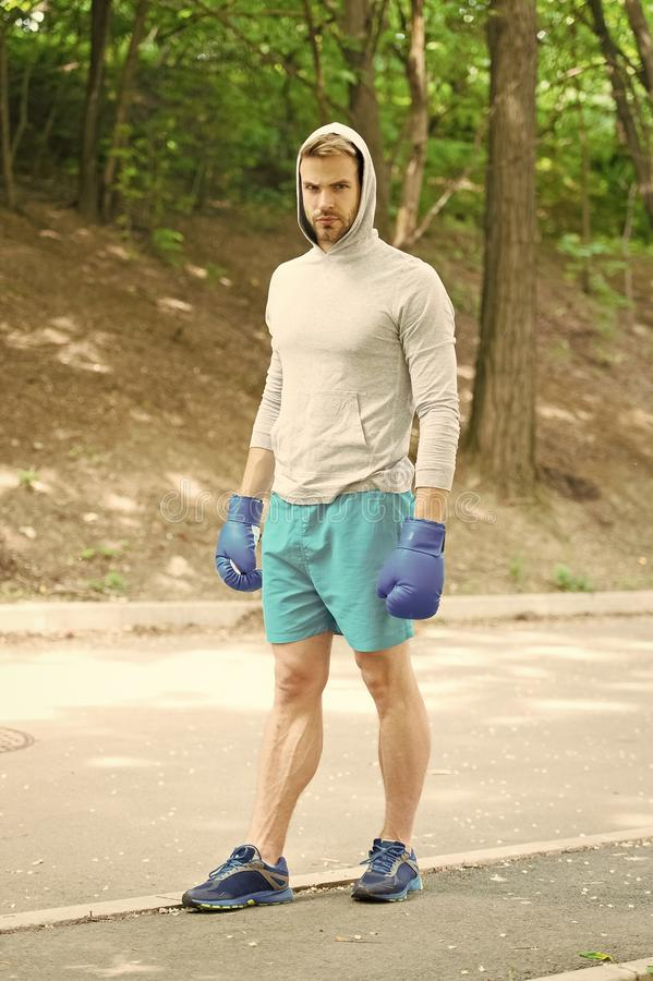 Big day is coming. Man athlete on concentrated face with sport gloves ready practicing boxing punch nature background stock images
