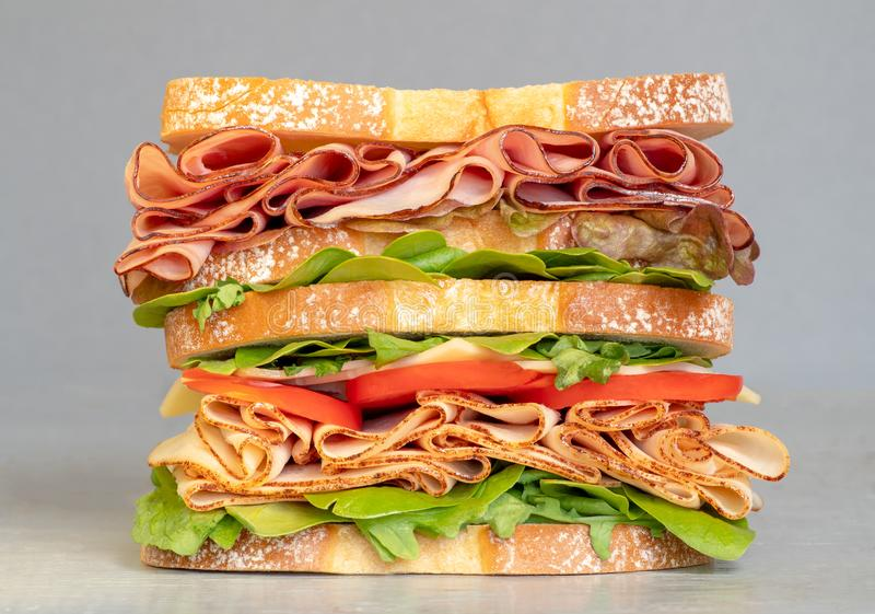 Big deli meat sandwich stuffed with cheese, ham, tomato. Club sandwich. Above view isolated on white background royalty free stock image