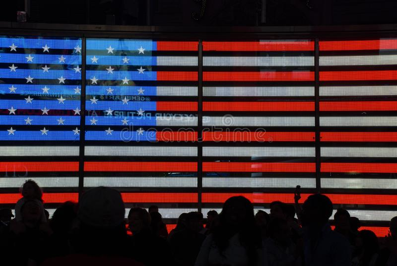 Big digital American flag on huge display on Times Square with silhouettes of people royalty free stock image