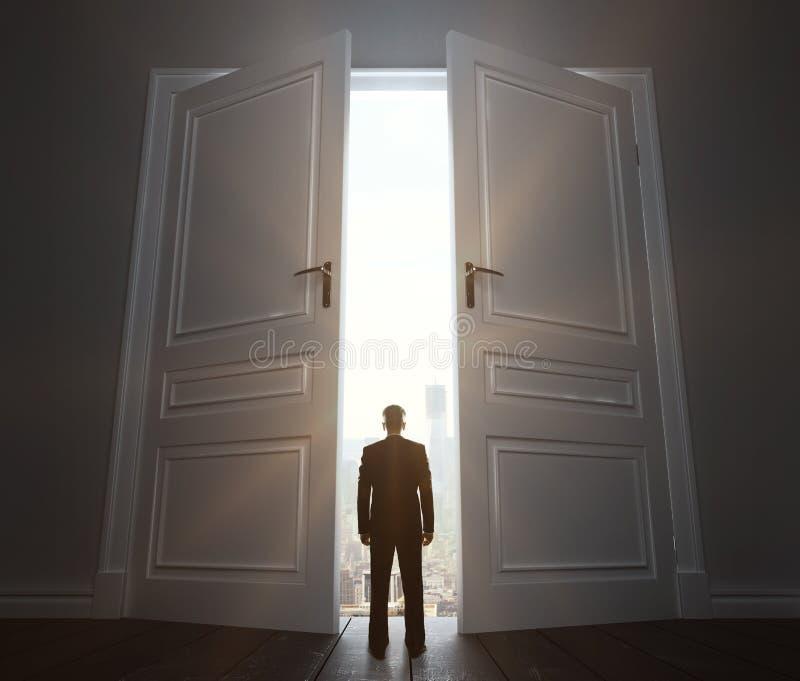 Big door to city. Businessman in room with big door to city royalty free stock photos