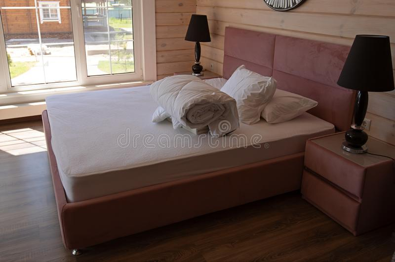Big double bed with two white pillows and white blanket in the luxury hotel stock photography