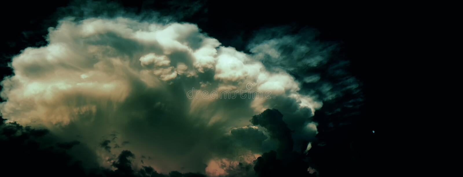 Big dramatic storm cloud probably cumulonimbus at summer twylight beside small moon on the right side royalty free stock photos