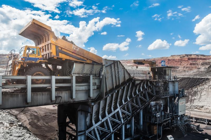 Big dump truck is mining machinery, or mining equipment to trans. Port coal from open-pit or open-cast mine as the Coal Production. Loading of coal ore from dump stock photography