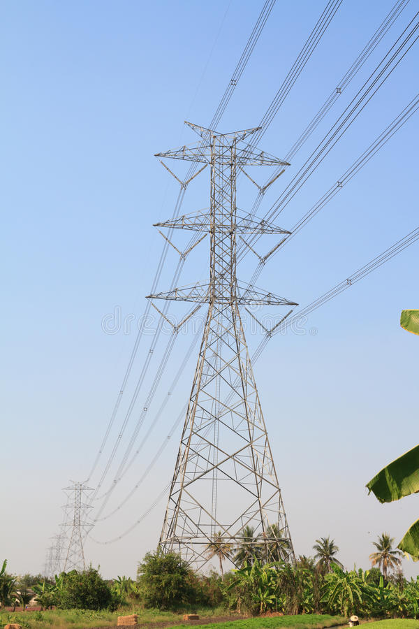 Big electric tower pole over banana farm and vegetable farm. Big electric tower pole over vegetable farm and blue sky royalty free stock images