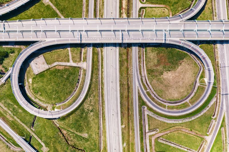 Big empty road junction on green land aerial view. Highway and half clover leaf junction with traffic royalty free stock photos