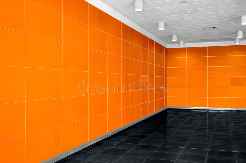Big empty room interior with bright orange wall, whire ceiling a stock image