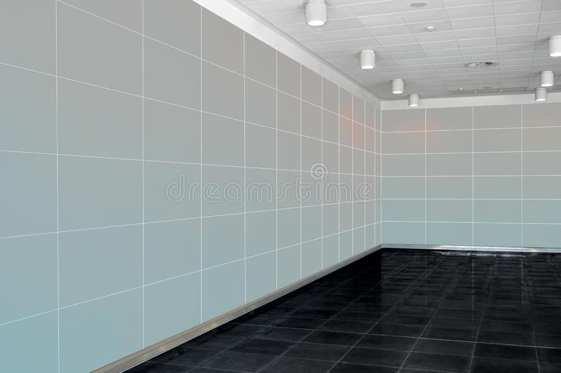 Big empty room interior with light grey wall, whire ceiling and stock photos