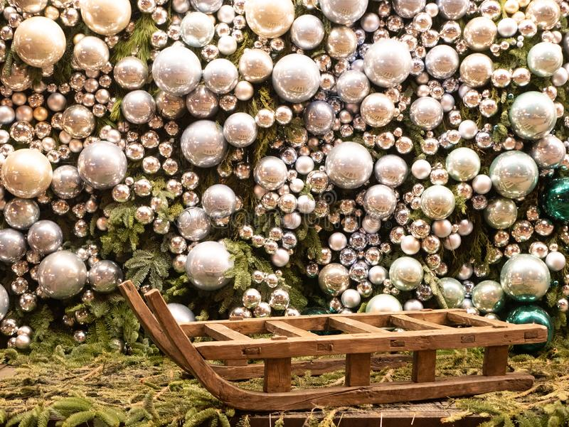 Big empty sleigh with huge shiny glass decorative silver color balls covered entire wall on background stock photography