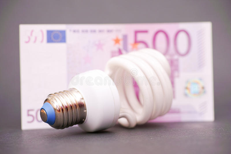 Big energy savings. Energy saving light bulb infront of a 500 euro banknote, as a concept for saving money on electricity - focus is on the bottom part of the stock photo
