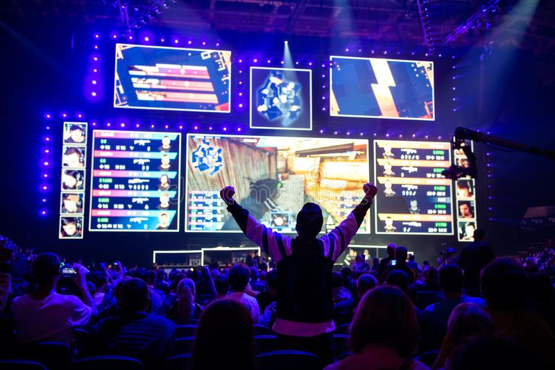 Big esports event. Video games fan on a tribune at tournament`s arena with hands raised. Cheering for his favorite team. stock images
