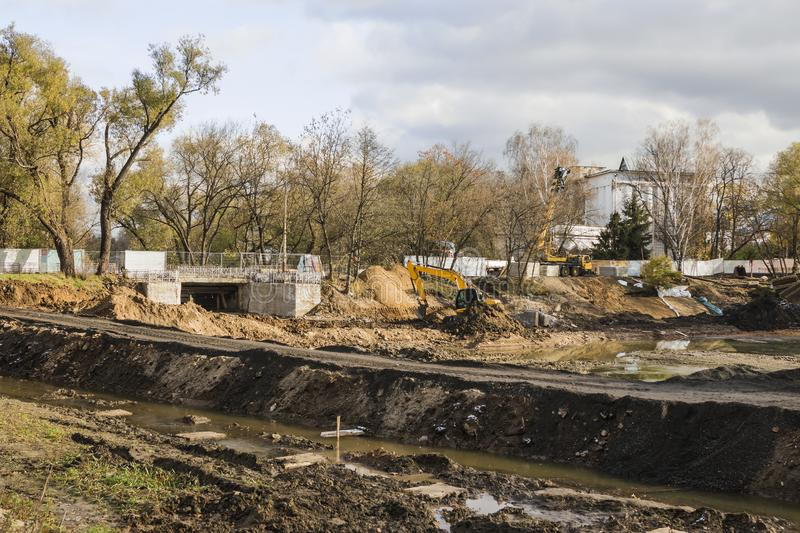 Big excavator during earthmoving works outdoors at construction site. Yellow excavator clears the river bed for the device pond. A. Ll-Russian exhibition center stock photography