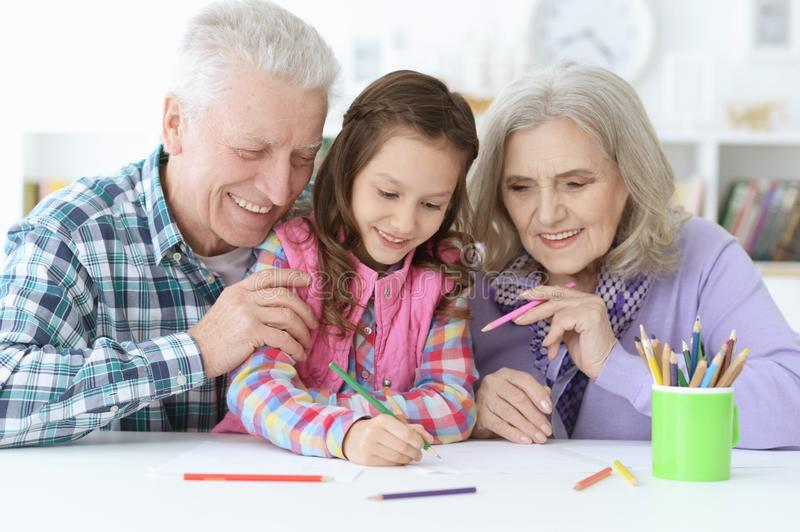 Big family with cute little girl doing homework royalty free stock photo