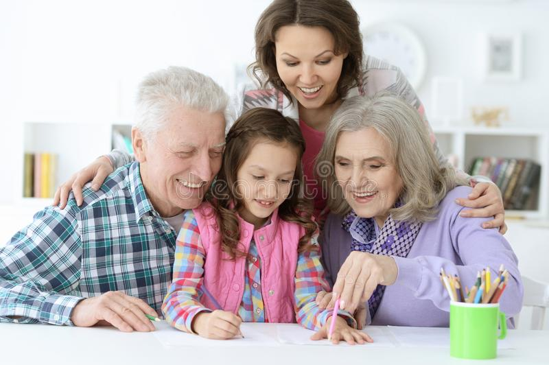 Big family with cute little girl doing homework stock image
